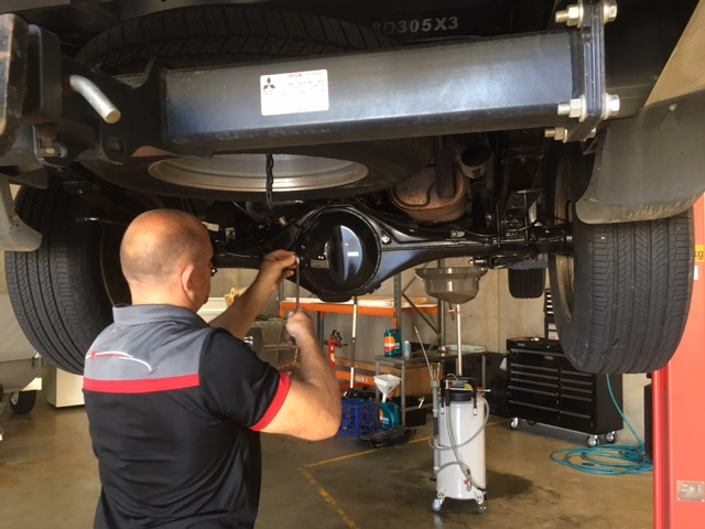 michael owner of airport automotive service performing mechanical repairs on four wheel drive vehicle